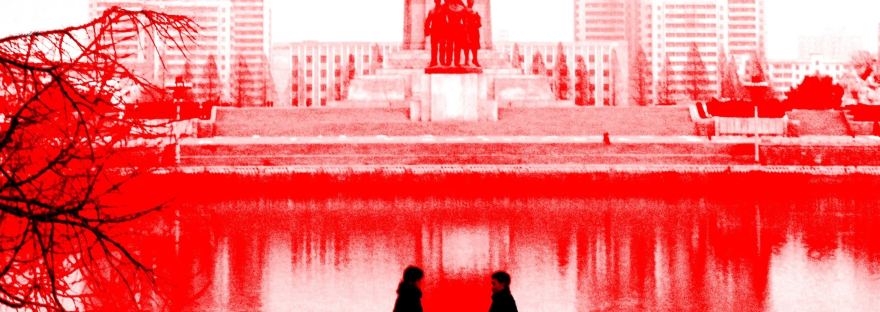 A false-colour photograph of two people talking in front of the Juche Tower in Pyongyang, North Korea.