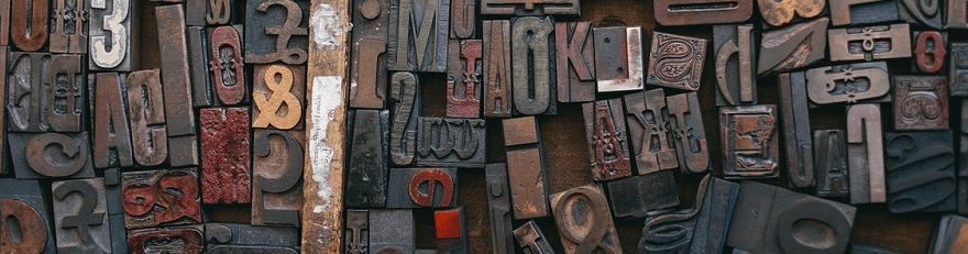 A photograph of wooden typesetting letters.